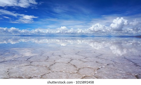 Unreal reflection of the sky and clouds on the lake Salar de Uyuni with a thin layer of salt and water, Altiplano of Bolivia