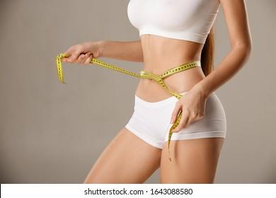 Unwiderrufliche schlanke gerbte Frau mit Maßband um die Taille. Perfperfekter, schlacker Körper - ein Beispiel für Sport, Diät, Fitness oder plastische Chirurgie und ästhetische Kosmetologie