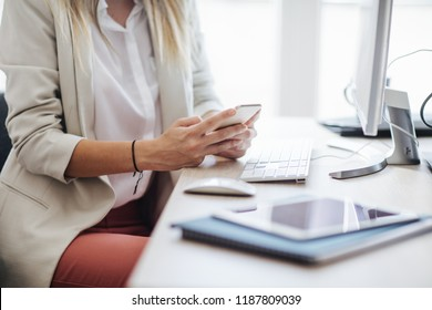 Unrecognisable businesswoman using a mobile phone in front of the desktop computer at the modern office space.