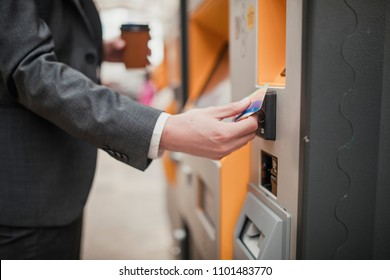 Unrecognisable person paying for a train ticket with contactless payment at a ticket machine.
