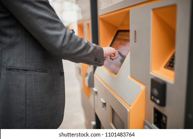 Unrecognisable person using a touch screen ticket machine and selecting which ticket they want.