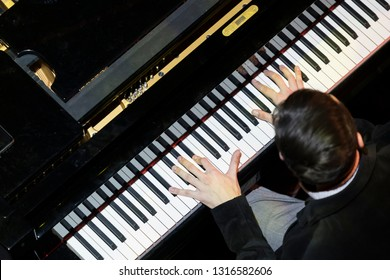 Unrecognisable pianist playing in jazz lighting