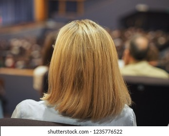 Unrecognisable woman attending an event, seen from behind