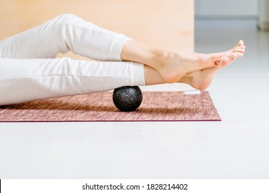 Unrecognisable woman using massage ball for muscle soreness after fitness exercise, muscle strain after high-intensity workouts, and physical and mental exertion after sitting in the office.