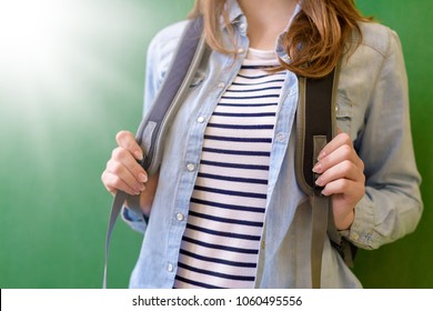 Unrecognisable young female high school student with rucksack leaning against blackboard at school. Back to school, Education, Teenagers concept.
