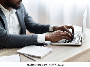 Unrecognizable african american employee working on laptop in modern office, hands typing on computer keyboard. Side view with copy space