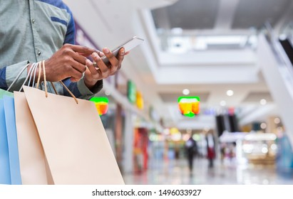 Unrecognizable african american guy with cellphone and purchases in shopping mall, panorama, copy space