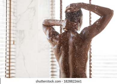Unrecognizable African American Man Taking Shower Washing Body Standing Back To Camera Under Falling Water Drops In Modern Bathroom Indoor. Male Bodycare, Wellness And Spa. Back View, Copy Space