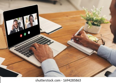 Unrecognizable african american man watching business webinar at laptop and writing notes in modern office, collage