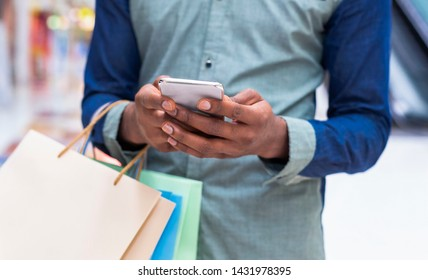 Unrecognizable african guy with shopping bags using cellphone at mall center, panorama, copy space
