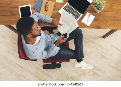 Unrecognizable african-american businessman working in modern office, reading reports, top view, copy space