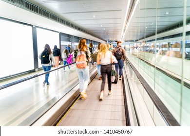 Unrecognizable airport and unrecognizable people going for their flights, long corridor with moving walkway, motion blur