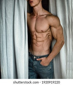 Unrecognizable, anonymous sexy shirtless muscular young man next to window curtains during the day, wearing only jeans