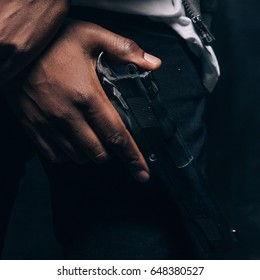 Unrecognizable armed black criminal man closeup studio shoot. Gangster guy with gun in hand on dark background. Outlaw, ghetto, murderer, robbery concept
