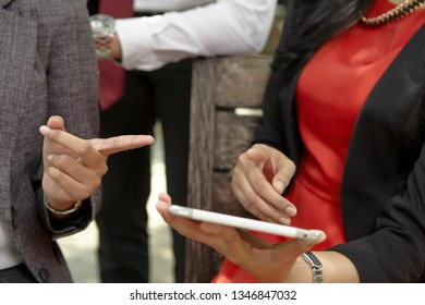 unrecognizable Asian business people using tablet in the park