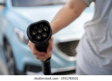 Unrecognizable Asian woman holding AC type 1 EV charging connector at EV charging station, woman preparing an EV - electric vehicle charging connector for recharge a vehicle.
