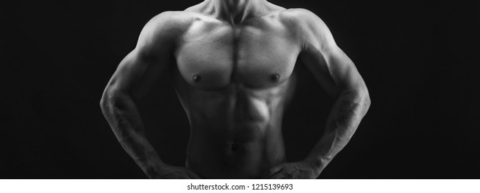 Unrecognizable athletic man, bodybuilder. Naked torso, muscular body. Strong chest and shoulder muscles. Studio shot on black background, low key. Bodybuilding concept, black and white image, crop