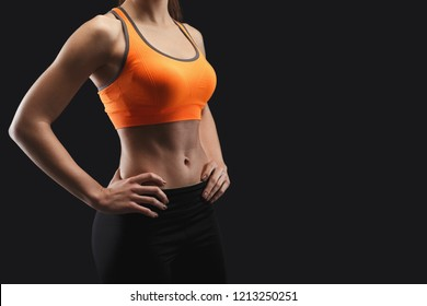 Unrecognizable athletic woman, bodybuilder. Naked torso, muscular body. Studio shot on black background, low key. Bodybuilding concept, copy space