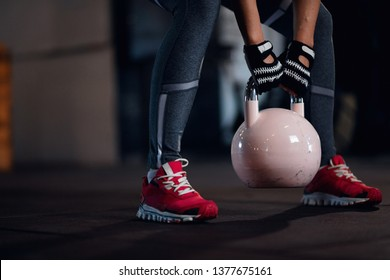 Unrecognizable athletic woman having cross training and exercising with kettle bell in health club.