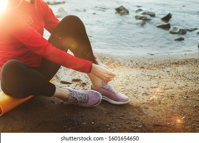 Unrecognizable Athletic Young Woman Sitting On A Rug And Tying Shoelaces Near The Sea, While Pausing During Exercises