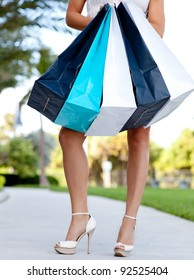 Unrecognizable attractive woman holding shopping bags - outdoors