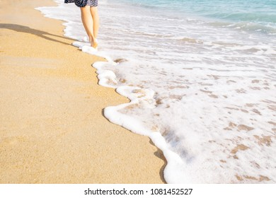 Unrecognizable barefoot young woman walking on sand beach near the sea, view of legs.