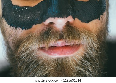Unrecognizable bearded adult man having coal carbon face mask. Blackheads, acne treatment. Male in beautician taking care of his skin.