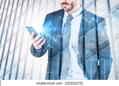 Unrecognizable bearded businessman looking at his smartphone standing over skyscraper background with graph. Stock market concept. Toned image double exposure