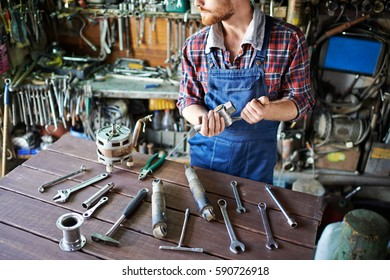 Unrecognizable bearded mechanic standing looking away and sorting working tools on table  in garage workshop
