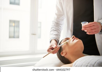 Unrecognizable beautician making facial treatment on woman face lying with eyes closed.