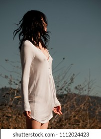 Unrecognizable, beautiful Asian woman wearing sheer white shirt that reveals the outlines of her breasts and nipples, standing in nature and enjoying the warm sun.
