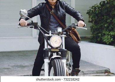 Unrecognizable biker wearing black leather jacket pressing gas pedal while sitting on vintage motorcycle ready for searching adventures