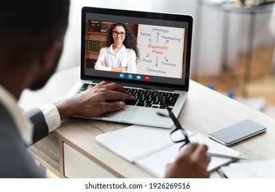 Unrecognizable black businessman working on laptop at his workplace in modern office interior, african american manager having online business training. Over shoulder shot, selective focus on device
