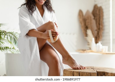 Unrecognizable Black Woman Dry Brushing Legs Making Anti-Cellulite Massage Sitting On Bathtub In Bathroom Indoor, Wearing Bathrobe. Body Care Routine. Cropped Shot, Selective Focus