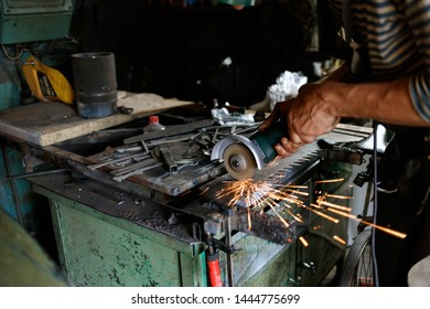 Unrecognizable blacksmith sawing metal with hand circular saw at forge, workshop. Blacksmithing concept