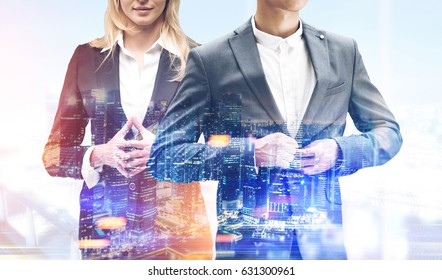 Unrecognizable blond businesswoman and a businessman buttoning his suit are standing against a foggy city panorama. Toned image, double exposure