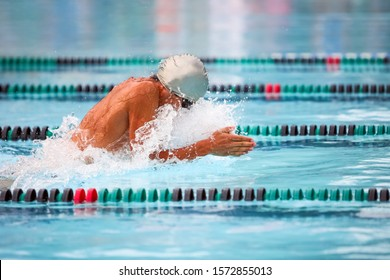 Unrecognizable breaststroke swimmer in a race, focus on water splash