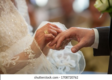 An unrecognizable bride and groom exchanging of the Wedding Rings in church during the christian wedding ceremony