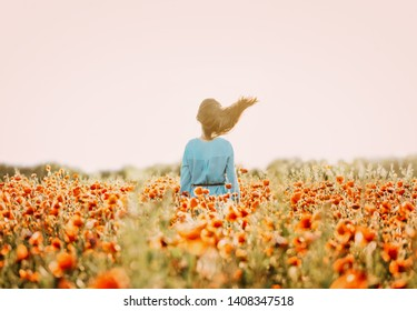 Unrecognizable brunette woman with fly-away hair standing in red poppy flower meadow in windy weather in summer, rear view.