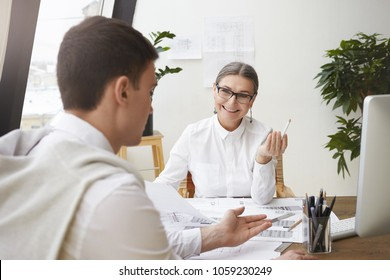 Unrecognizable brunette young male architect sitting at desk with drawings while discussing something with his cheerful mature female boss who is smiling at him, approving his creative ideas
