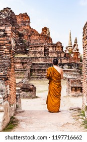 A unrecognizable buddhist monk meditating and beholding the ancient Ayutthaya ruins in the famous Ayutthaya Historical Park, Thailand