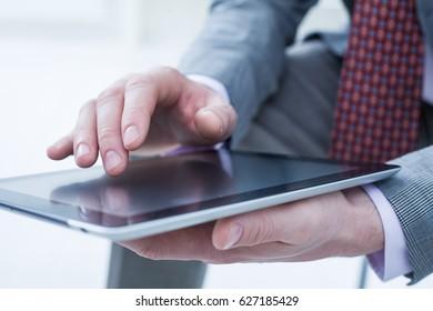 Unrecognizable business man holding a digital tablet