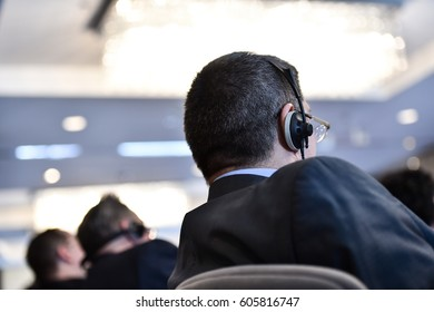 Unrecognizable business people using headphones for translation during event