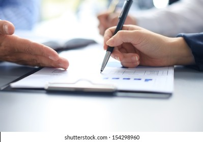 Unrecognizable business person analyzing graphs and taking notes