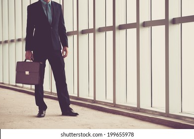 Unrecognizable businessman with a briefcase standing in the office building