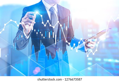 Unrecognizable businessman with clipboard drawing forex graph standing over blurred cityscape background. Toned image double exposure