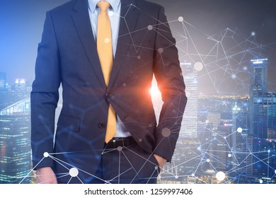 Unrecognizable businessman in dark suit and yellow tie standing over night cityscape background with double exposure of network hologram. Toned image