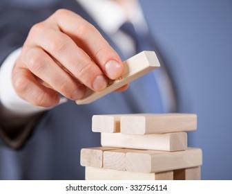 Unrecognizable businessman forming a wooden pyramid - closeup shot