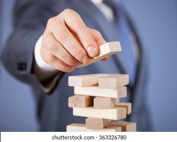 Unrecognizable businessman forming a wooden pyramid - closeup shot