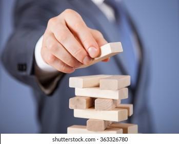 Unerkennbarer Geschäftsmann, der eine Holzpyramide bildet - Nahaufnahme
